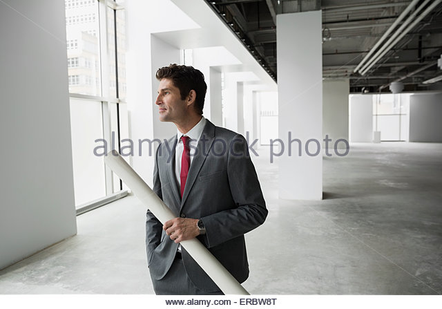 Architect holding blueprints in empty office - Stock Image