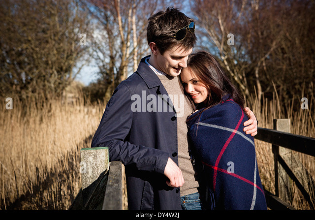 Romantic couple standing on footbridge - Stock-Bilder