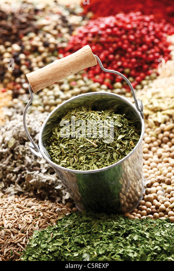 A selection of spices, in foreground dried sage in zinc bucket, close-up - Stock Image