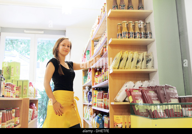 Woman working in organic food market, stacking shelves - Stock Image