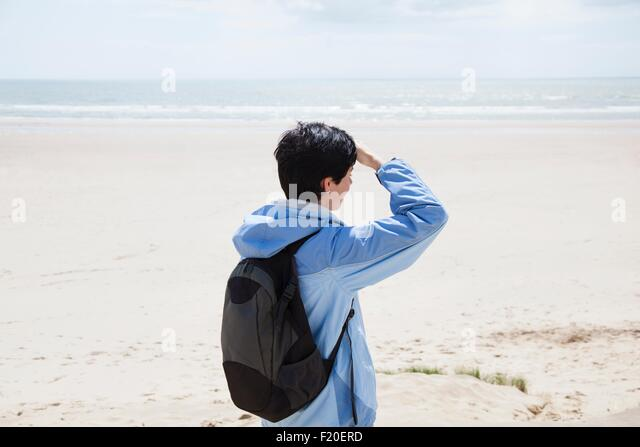 Mid adult woman on beach shielding eyes whilst looking out to sea - Stock Image