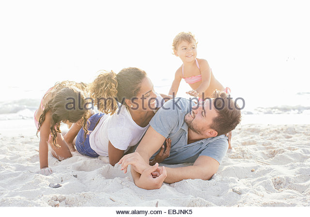 Couple with two girls play fighting on beach, Tuscany, Italy - Stock-Bilder