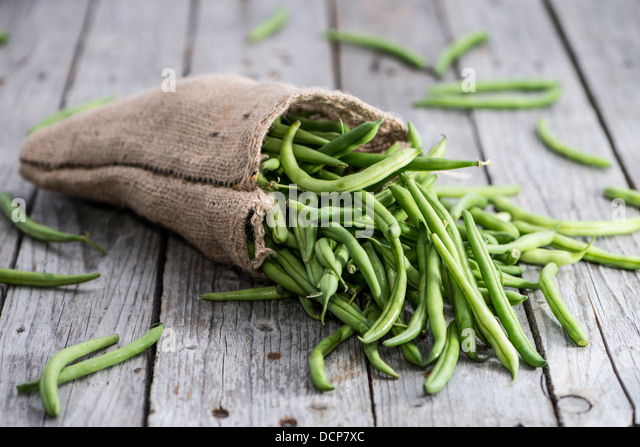 Some Green Beans on wooden background - Stock Image