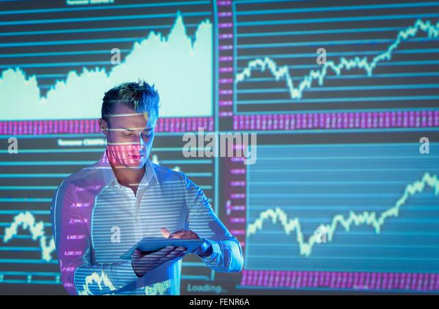Businessman using digital tablet and making presentation with graphical projected images - Stock Image