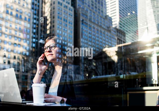 Businesswoman using phone seen through window with reflection of building - Stock-Bilder