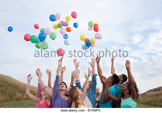 Young people releasing balloons - Stock Image