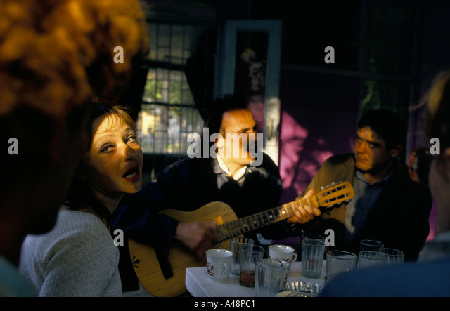 woman singing along with man playing guitar sitting in a cafe in simferopol Crimea ukraine - Stock Image