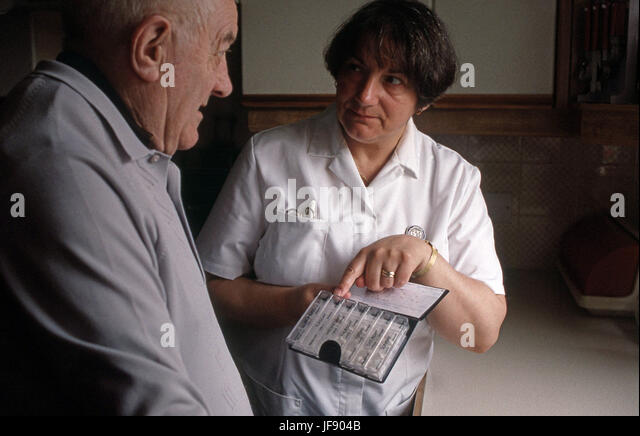 Health visitor assisting elderly man with his medication management - Stock Image
