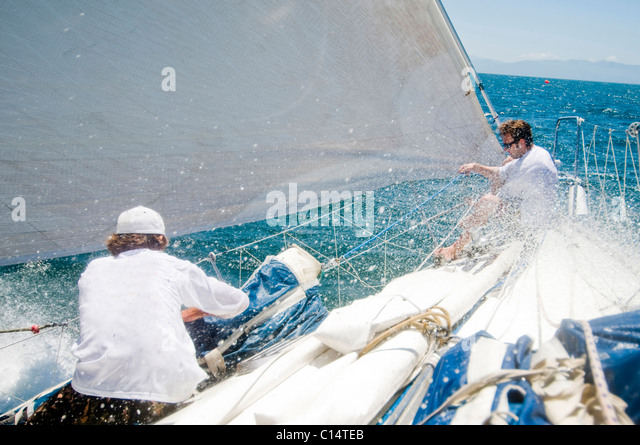 Two sailors preparing a sail during a race - Stock Image