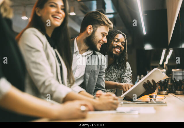 People discussing article in a pub after work - Stock Image