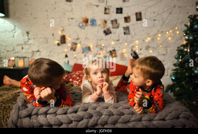 Caucasian girls and boy laying on bed near Christmas tree - Stock Image
