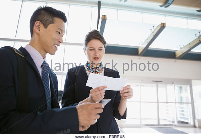Airport customer service representative helping businessman - Stock Image