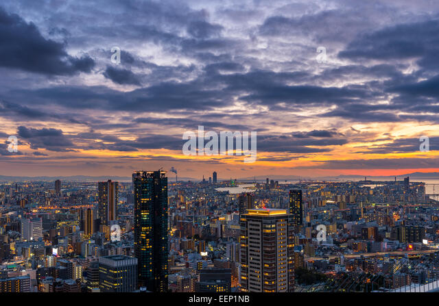 The sun sets over the vast cityscape of Osaka, Japan. - Stock Image