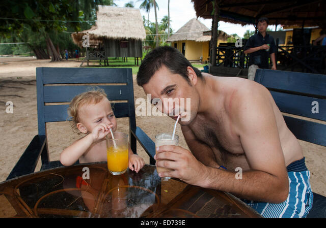 Taking breakfast in Beach on the island of Koh Russei. Cambodia. Travel with children's.  Father traveling with - Stock Image