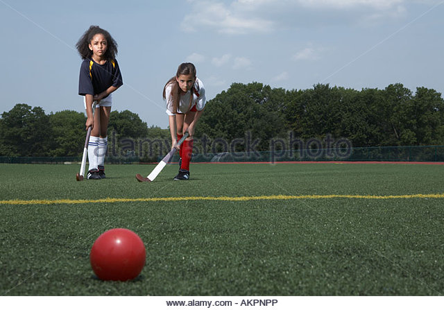 Two girls playing hockey - Stock Image