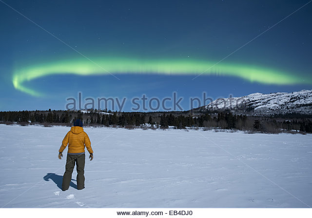 A man enjoying a view of the northern lights, or Aurora Borealis, over a snowy landscape. - Stock-Bilder
