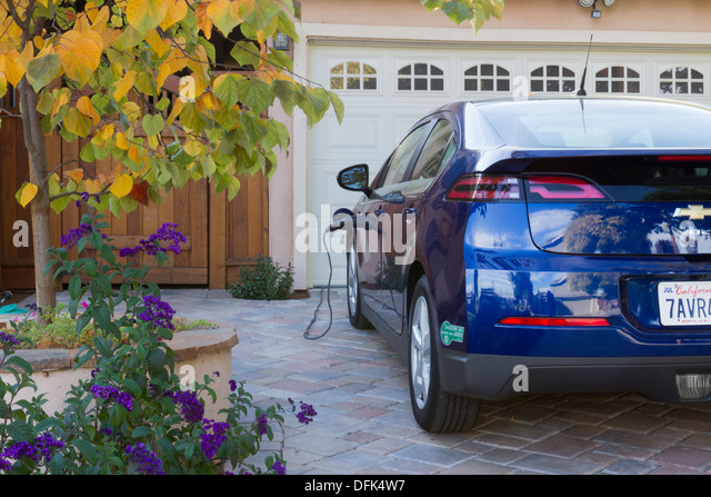 Plug-in electric car with carpool sticker parked in driveway, with connector plugged in and charging at home - Stock Image