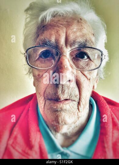 Elderly woman suffering from macular degeneration in her eyes - Stock Image