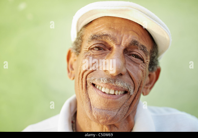 portrait of senior hispanic man with white hat looking at camera against green wall and smiling. Horizontal shape, - Stock-Bilder