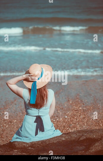 Beautiful young historical girl sitting on the beach in a blue dress and wearing a straw hat - Stock Image