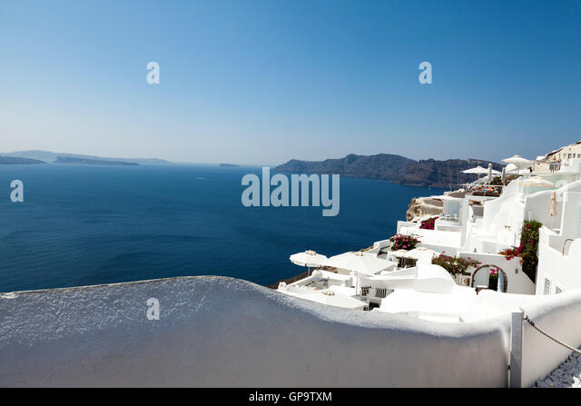 Traditional white buildings on the vibrant, hot and sunny Greek Island of Santorini set against a beautiful blue - Stock Image