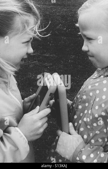 Two girls exchange glares at one another over their electronic devices. - Stock Image