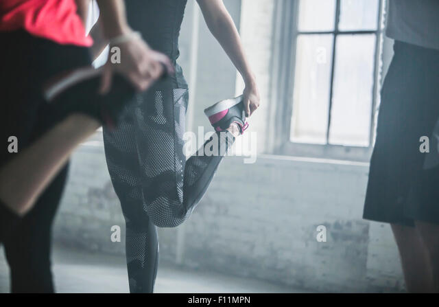 Athletes stretching legs in gym - Stock Image
