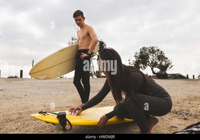 Two friends on beach, woman waxing surfboard, man standing beside her holding surfboard - Stock-Bilder