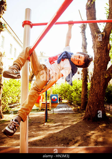 little cute blond boy hanging on playground outside, alone train - Stock Image