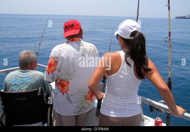 Miami Beach Florida Atlantic Ocean water charter fishing boat onboard Hispanic man woman wheelchair disabled couple - Stock Image