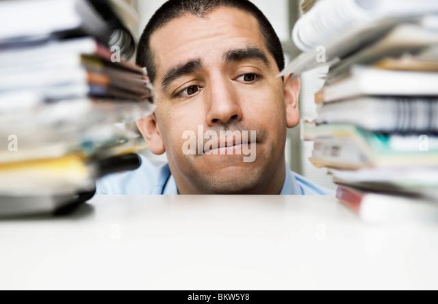 Man between pile of books - Stock Image
