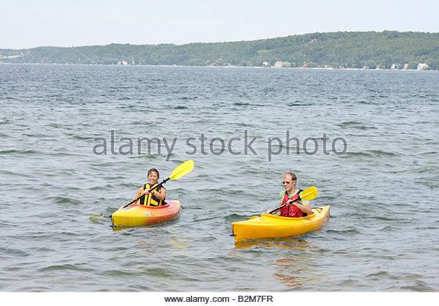 Michigan Traverse City West Arm Grand Traverse Bay Clinch Park kayak man woman water sport recreation oars paddle - Stock Image