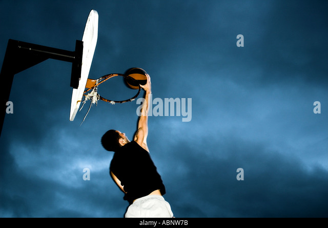 A basketball player dunking a basketball. Dark, cloudy sky in the background. - Stock Image