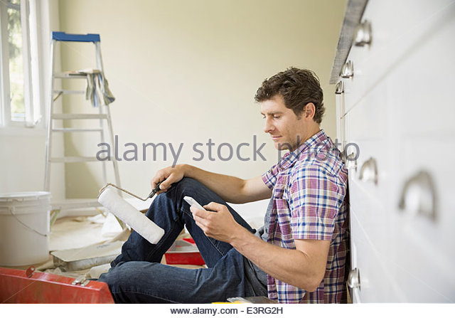 Man with paint roller text messaging - Stock Image
