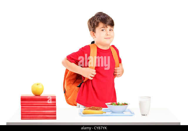 A schoolboy preparing for lunch isolated on white background - Stock Image