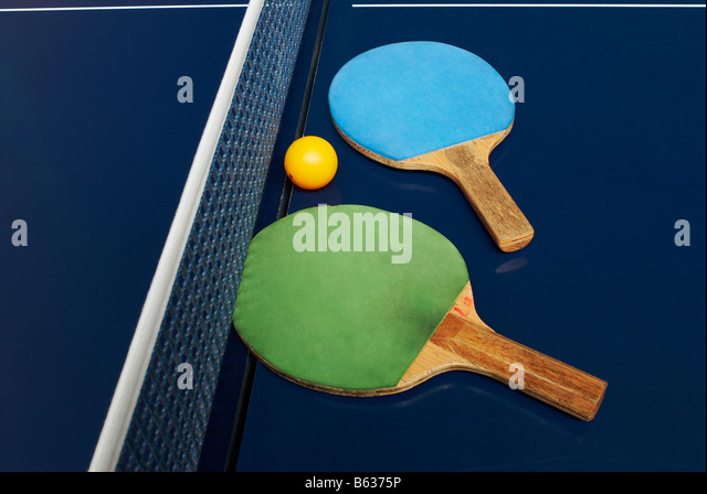 Two table tennis rackets with a ball on a table tennis table - Stock Image