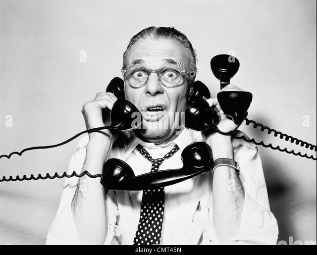 1950s 1960s PORTRAIT OF FRAZZLED BUSINESSMAN TRYING TO ANSWER FOUR BLACK TELEPHONES PHONES AT ONCE - Stock Image