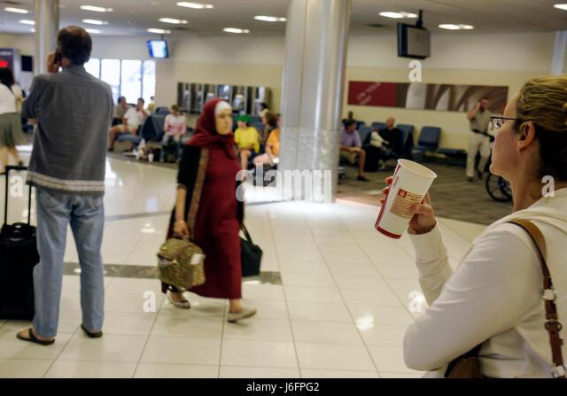 Atlanta Georgia Hartsfield-Jackson Atlanta Airport ATL concourse passenger woman women Muslim hijab coffee cup gate - Stock Image