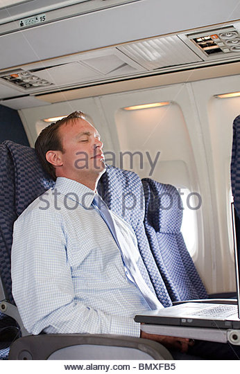 Businessman sleeping in an airplane - Stock Image