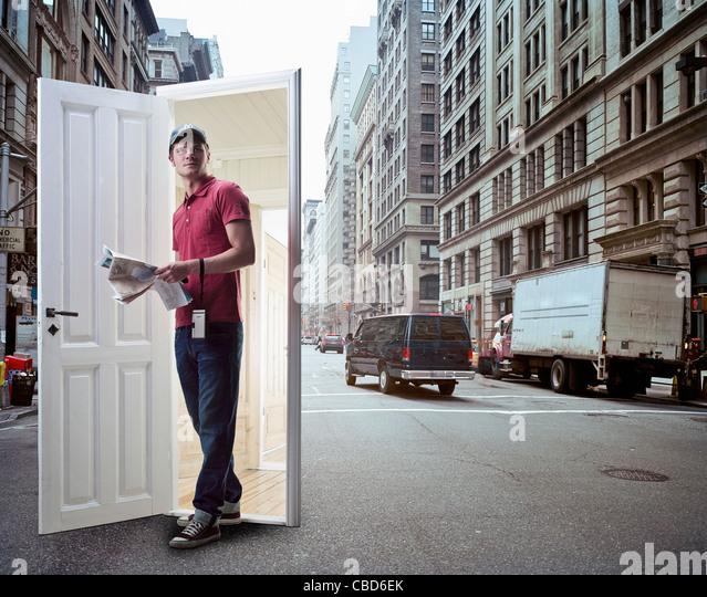 Man emerging from door on city street - Stock Image