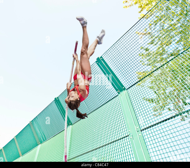 Athlete vaulting over wire fence - Stock Image