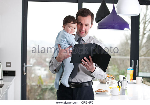 A father and baby son looking at a digital tablet - Stock-Bilder