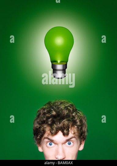 A young man with a green lightbulb over his head - Stock Image