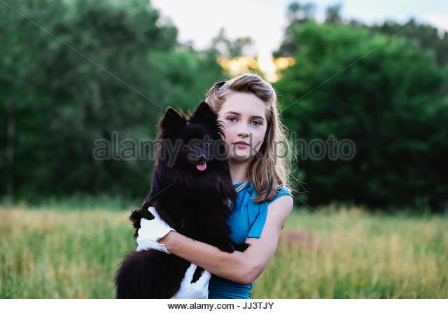 Teen girl and her Pomeranian dog - Stock Image