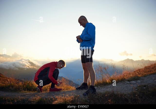 Trail runners resting, one tying shoelace, Valais, Switzerland - Stock Image
