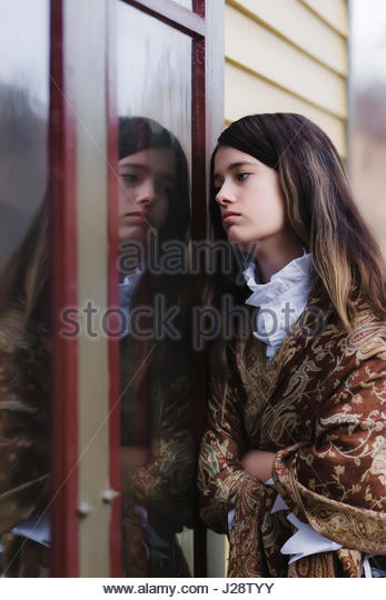 Brunette young woman looking into window - Stock Image