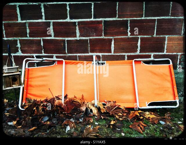 Orange lawn chair leaning against a brick wall surrounded by fall leaves. - Stock Image