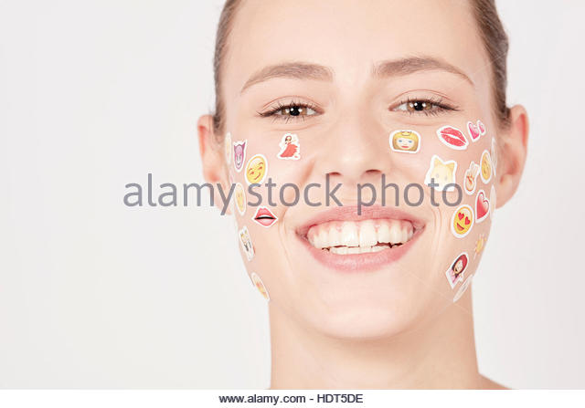 Smiling teenage girl with emoji stickers on her face. - Stock Image