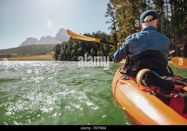 Rear view image of a man canoeing in a lake. Man paddling a kayak on summer day. - Stock Image