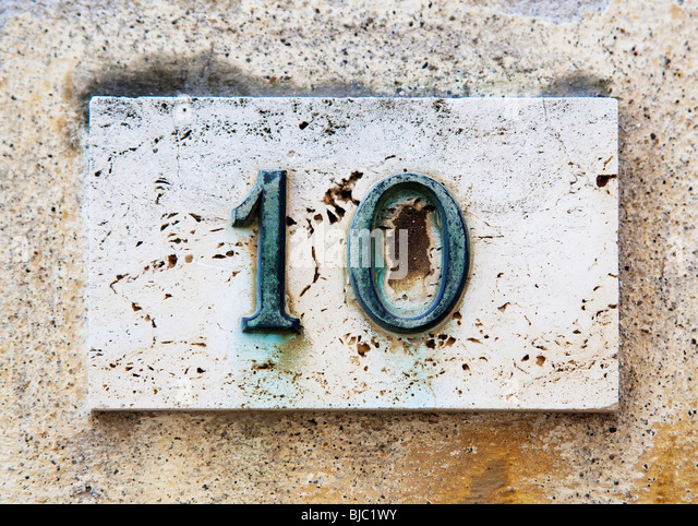Block number on a weathered wall - Stock Image